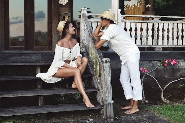 Young lovely couple wearing natural clothes  sitting on the porch of their house