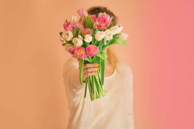 カラフルな新鮮な花のチューリップと白いドレスの若い素敵な女の子