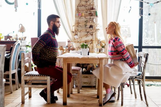 젊은 사랑스러운 힙 스터 레스토랑에 앉아 놀라움을 위해 자신의 뒤의 뒤에 선물을 들고 스웨터에 몇을 사랑 해요.