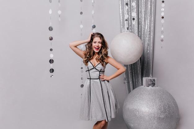 Giovane, adorabile donna in un bellissimo vestito da vacanza, sorridendo brillantemente contro lo scenario di capodanno, gioendo per le prossime vacanze