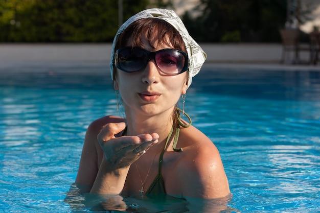화창한 여름날 지중해 리조트 수영장에서 포즈를 취하는 젊은 사랑스러운 여성