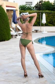 아름다운 화창한 여름날 지중해 리조트 수영장 근처에서 포즈를 취한 아름다운 젊은 여성