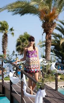 화창한 여름날 지중해 리조트 수영장 다리에서 포즈를 취한 젊은 여성