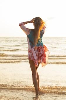Молодая милая женщина в красивом платье гуляет по берегу моря во время заката