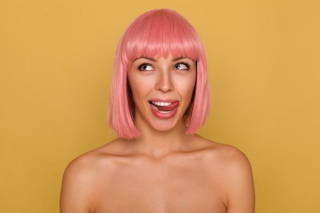 Giovane bella donna con corti capelli rosa che guarda allegramente verso l'alto e sporge la lingua mentre si trova sul muro di senape con le spalle nude