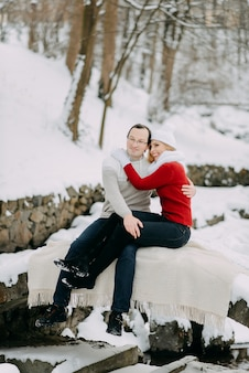 A young lovers couple in winter jackets and scarves sitting in a snow park