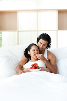 Young lovers eating strawberries