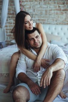 Молодые влюбленные мужчина и женщина в спальне на кровати.