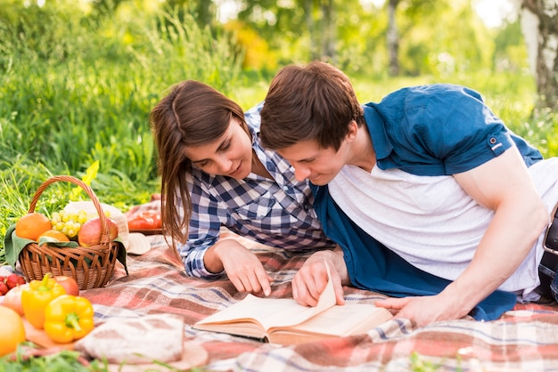 Young lovers reading book on blanket outside