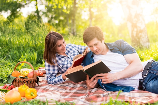 Young lovers resting on plaid and reading books