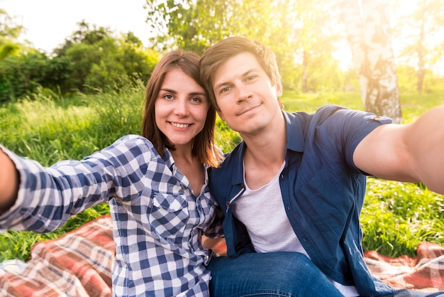 Young lovers sitting on plaid in forest and taking selfie