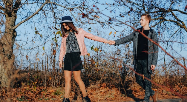 Молодые влюбленные гуляют рука об руку в лесу солнечным осенним вечером