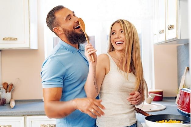 キッチンで一緒に料理をする若い愛情のあるカップル