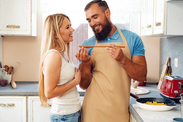 Young loving couple cooking together in kitchen at home