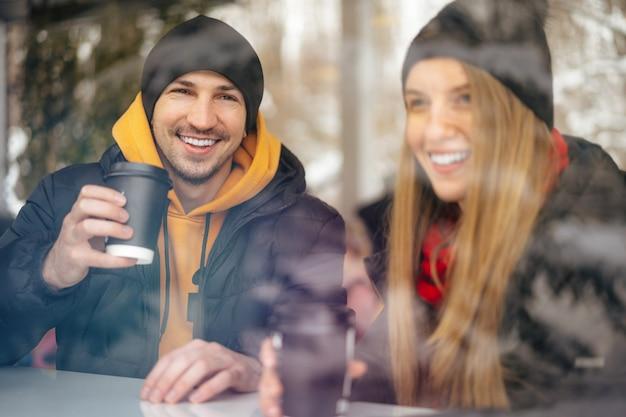 ガラスの後ろのカフェでコーヒーを飲む若い愛情のあるカップル