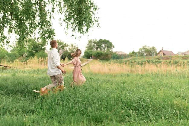若い愛するカップルが楽しんで、彼らの最愛の国内犬の品種ビーグルと野生の花の花束と芝生の緑の草の上を実行