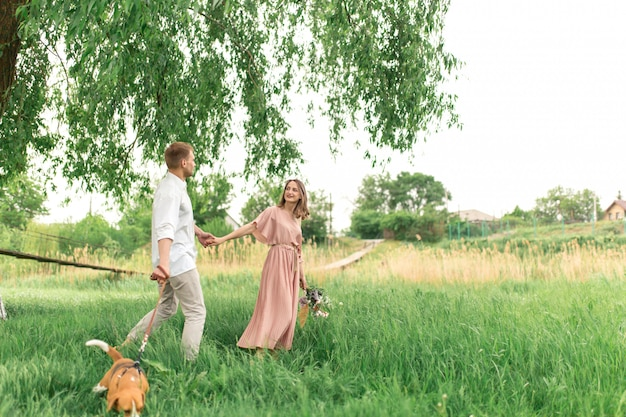 Young loving couple having fun and running on the green grass on the lawn with their beloved domestic dog breed beagle and a bouquet of wildflowers