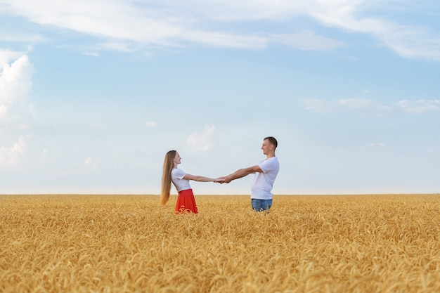 Young loving couple holding hands on background of wheat field.
