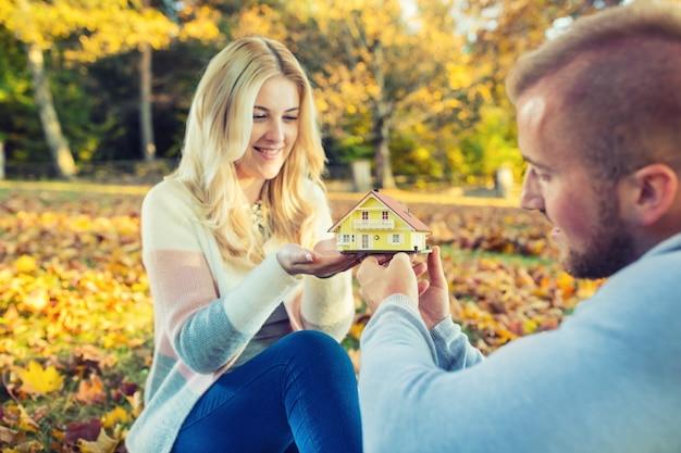 秋の庭や公園で小さなモデル家を保持している若い愛情のあるカップル。