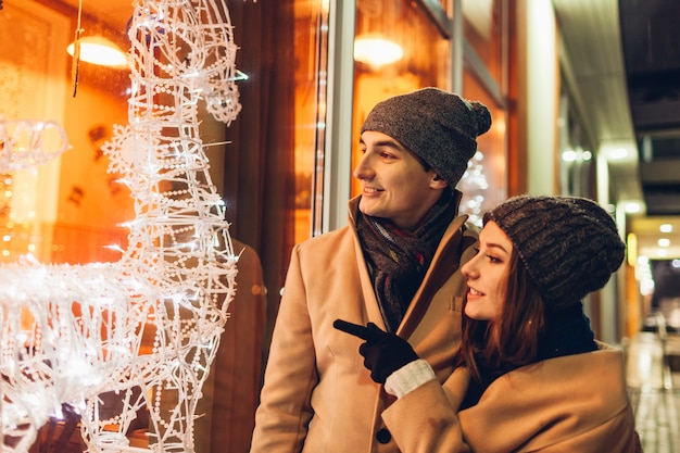 Young loving couple hugging by holiday cafe showcase with decorated reindeers at night