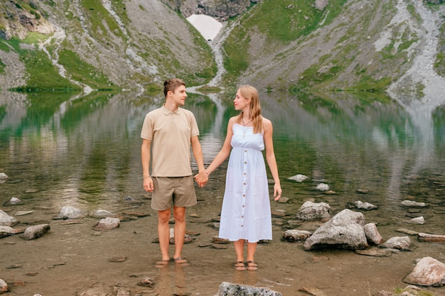Young loving couple hugging in cold lake among high mountains in summer day.