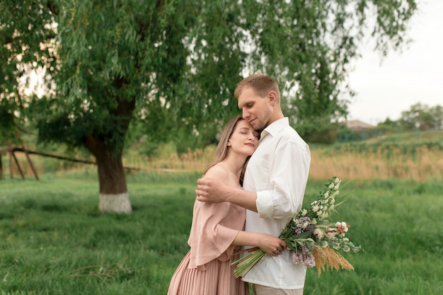 Young loving couple hugging and dancing on the green grass on the lawn. beautiful and happy woman and man gently touch each other. beautiful couple in love. girl in the dress and the guy in the shirt