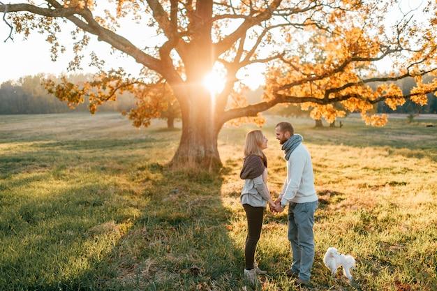 夕暮れの秋のフィールドで抱き締める愛情のあるカップル