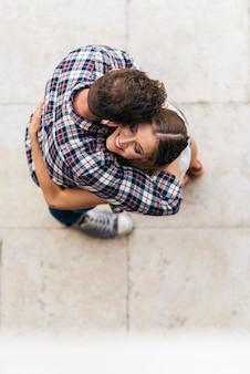 通りで抱き締める若い愛情のあるカップル。上面から。若い愛の概念。