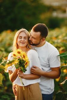Молодая влюбленная пара целуется в поле подсолнечника. портрет пары, позирующей летом в поле.