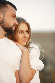 ひまわり畑で若い夫婦がキスします。フィールドで夏にポーズのカップルの肖像画。