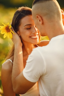 Young loving couple is kissing in a sunflower field. portrait of couple posing in summer in field.