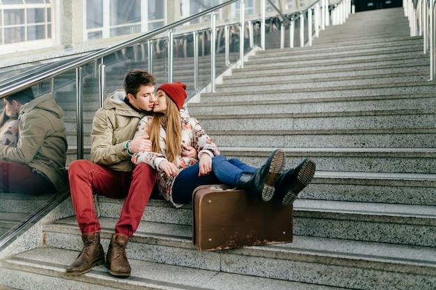 Молодая влюбленная пара поцелуи и сидя на лестнице.