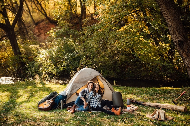Young loving couple make camp in the forest