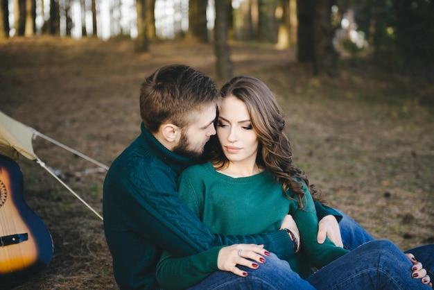 森のテントに対してキャンプファイヤーの近くに座って、キャンプする観光客の若い愛情のあるカップル