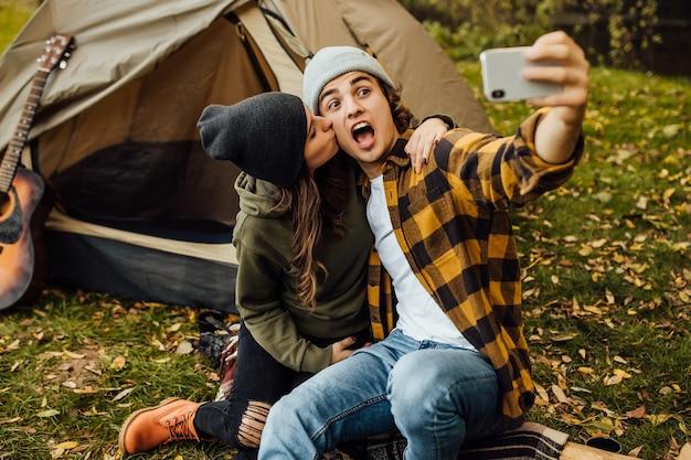 観光客の若い愛情のあるカップルは楽しんで、自然の中で火の近くで自分撮りをします