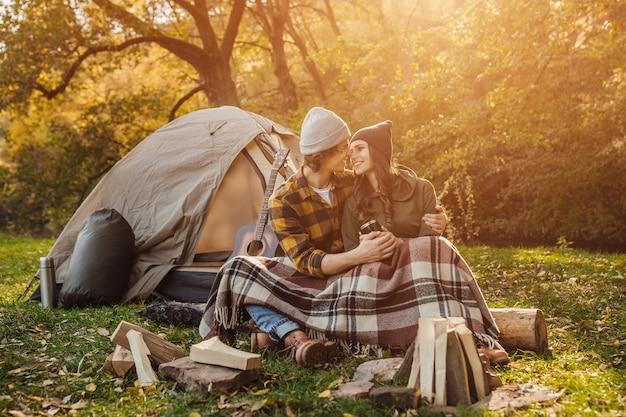 Молодая влюбленная пара туристов, отдыхающих у костра на природе