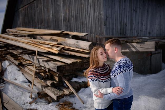 雪をかぶった山の頂上でデートの若い夫婦