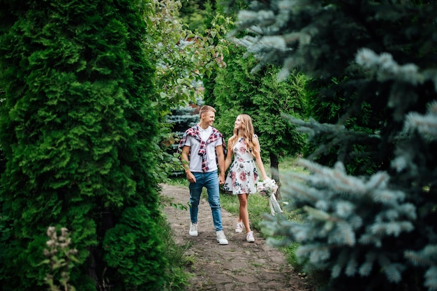 Giovani coppie amorose nel parco in una soleggiata giornata autunnale o estiva. guardandosi l'un l'altro.