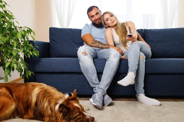 彼らの犬のペットと一緒にリビングルームでリラックスした若い愛情のあるカップル