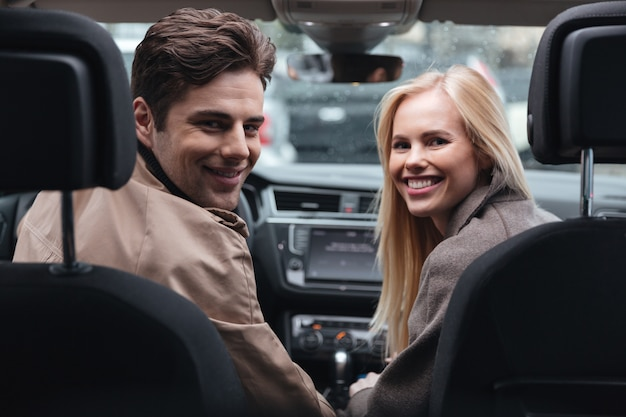 Young loving couple sitting in car looking back.