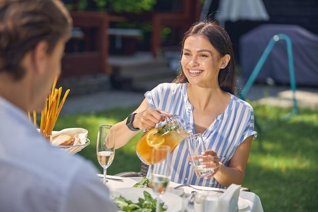 酒を飲みながら、お互いに話している間、ワインのグラスを持って公園で屋外でデートすることによってカフェに座っている若い愛情のあるカップル