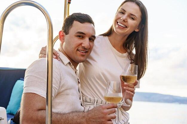 요트 갑판에 앉아 와인을 마시는 젊은 부부