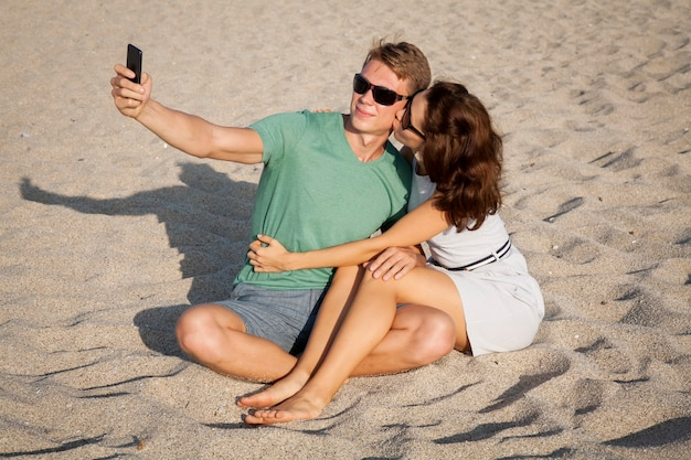 Young loving couple sitting on the sand at the beach, and the make sekfie by telephone.