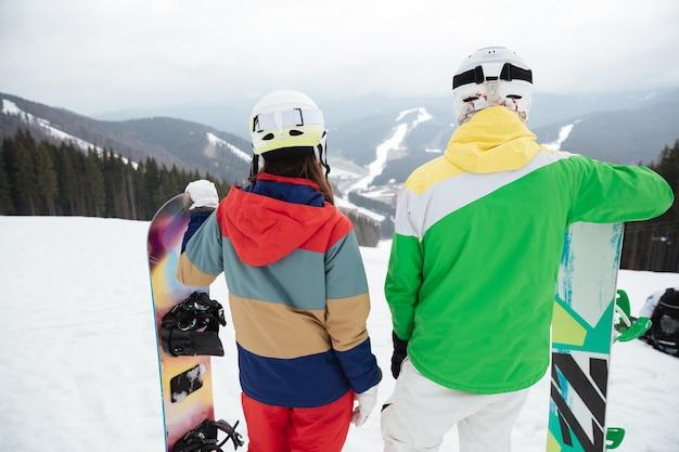 凍るような冬の日の斜面で若い愛情のあるカップルスノーボーダー