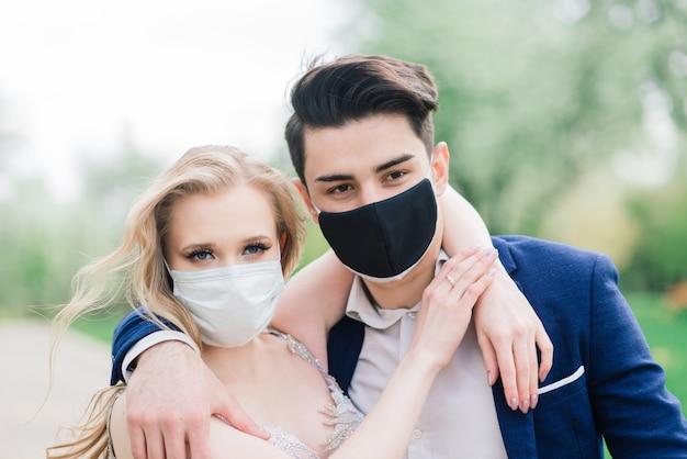 彼らの結婚式の日の検疫中に医療マスクを歩いている若い愛情のあるカップル
