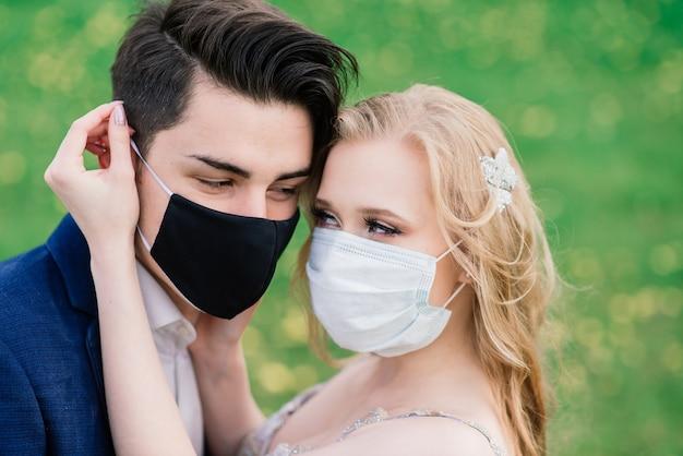 結婚式の日の検疫中に公園で医療マスクで歩く若い夫婦。コロナウイルス、病気、保護、病気。ヨーロッパのお祝いはキャンセルされました。