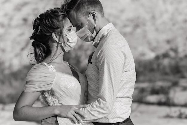 結婚式の日の検疫中に公園の医療マスクを歩いている若い愛情のあるカップル。