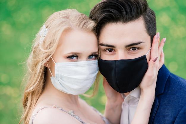 結婚式の日の検疫中に公園で医療マスクで歩く若い夫婦