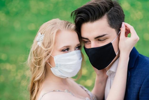 結婚式の日の検疫中に公園で医療マスクで歩く若い夫婦。