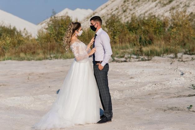 Молодая влюбленная пара гуляет в медицинских масках в парке во время карантина в день свадьбы.